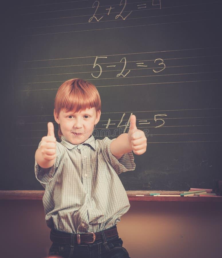 Rödhårig manskolpojke nära svart tavla arkivfoto