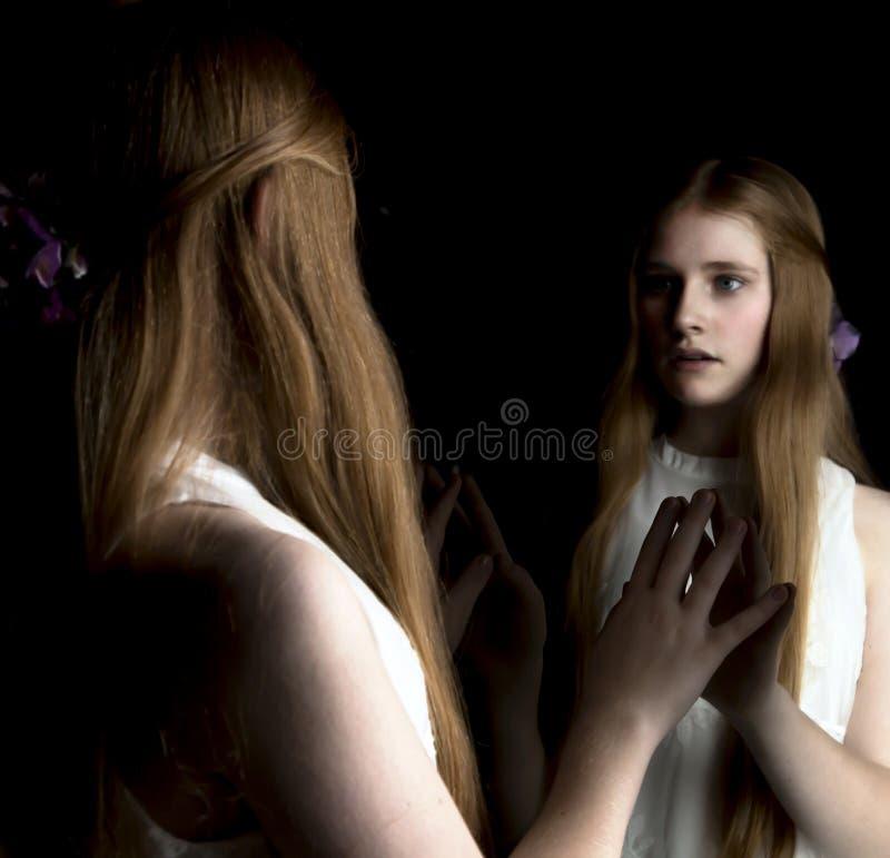 Rödhårig mantween som ser i spegel royaltyfri fotografi