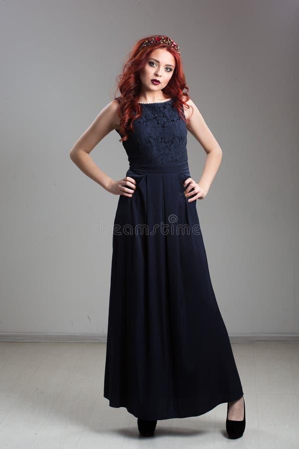 Rödhårig modell som poserar i aftonklänning och i diadem royaltyfri fotografi