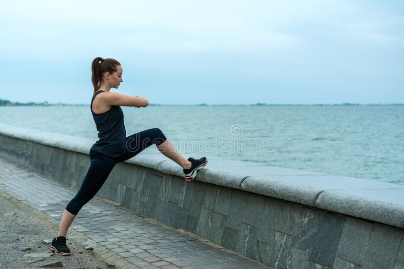 R?dh?rig n?tt flicka i fr?knar p? havsstranden som kopplas in i sportar, gymnastik utomhus- sportar royaltyfria bilder