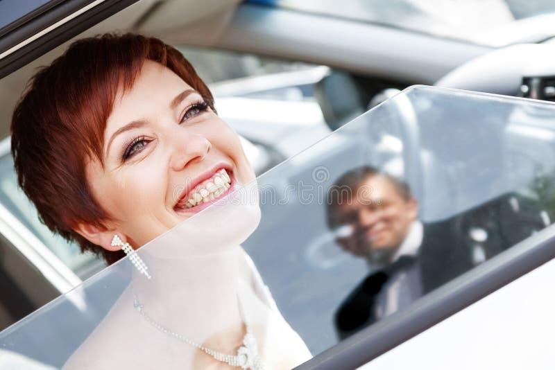 Rödhårig rolig brud i bilen som ler brudgummen Kvinna 35 år bröllop royaltyfria bilder
