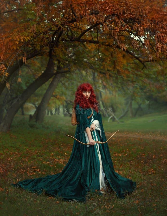 Rödhårig skönhet i sökandet av offret, legenden av Robin Hood, mystisk dam i lång regnrock för grön sammet med arkivfoton