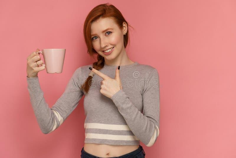Rödhåriga flickapunkter på hennes kopp som ler på kameran royaltyfri bild