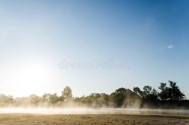 Rök avdunstning ovanför vattnet under den tidiga gryningen på floden royaltyfri bild