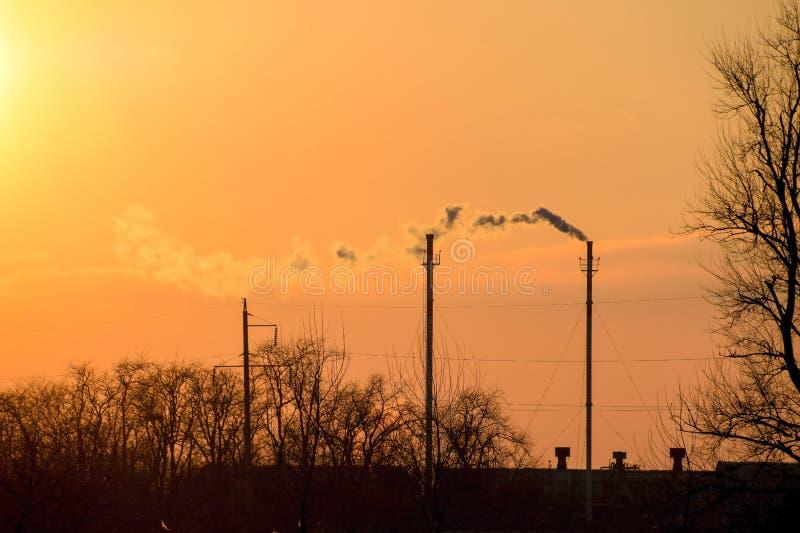 Rök från kokkärlrören på solnedgången för ligganderussia för 33c januari ural vinter temperatur arkivfoton
