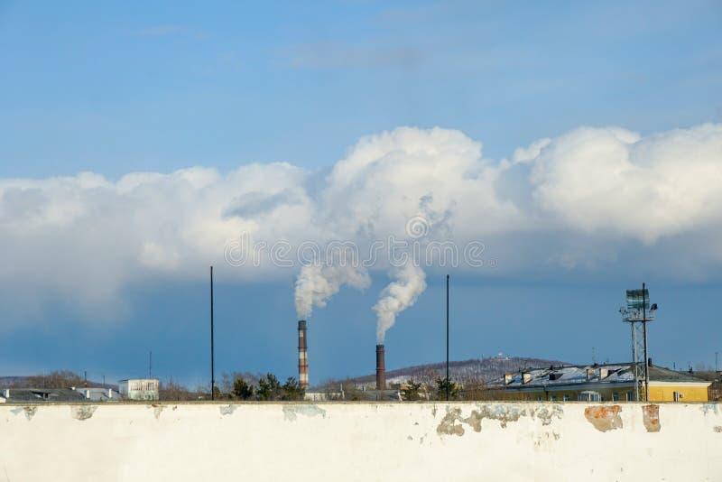 Rök kommer ner från rören av den termiska kraftverket, horisontellt royaltyfria bilder
