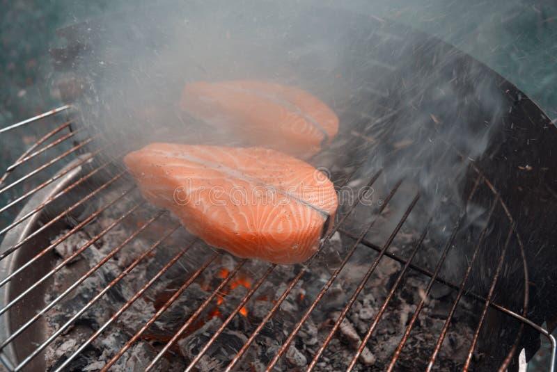 Rök och aska ovanför den grilla laxen fotografering för bildbyråer