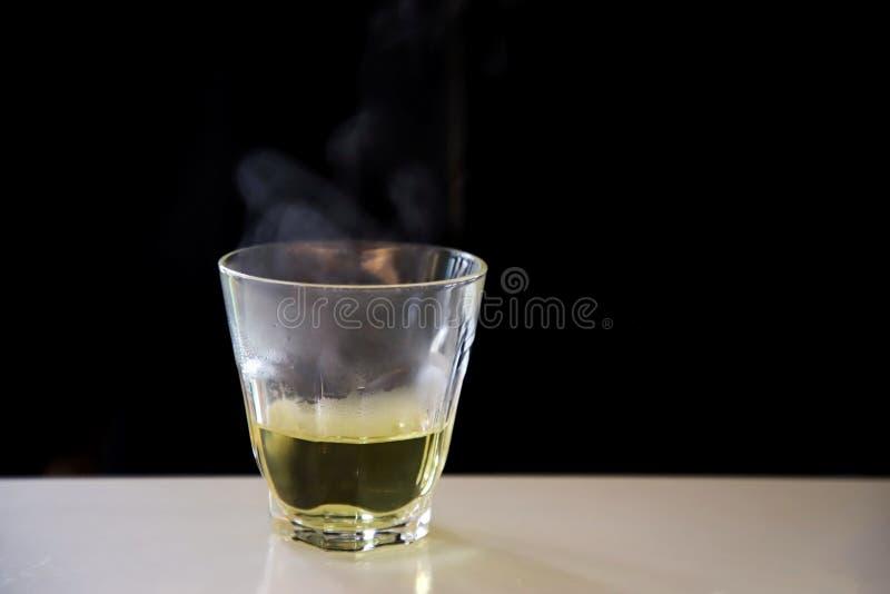 Rök varmt kinesiskt te baserat på ett genomskinligt glas placerat på ett vitt bord arkivfoton
