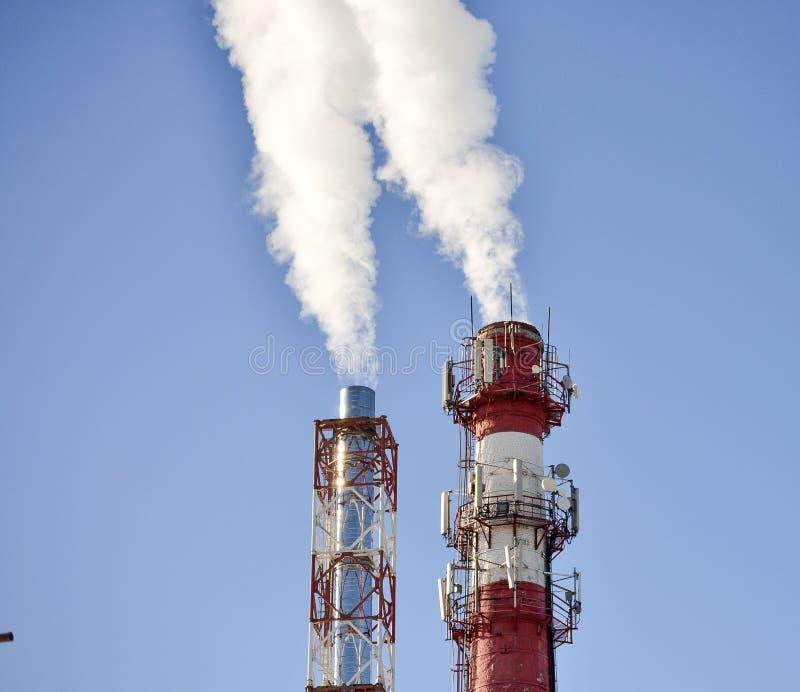 Röka ett rör av uppvärmningväxter som levererar värme till staden royaltyfria foton