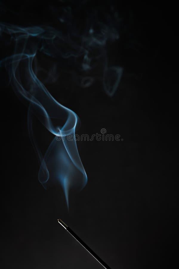 Röka rökelsepinnen med rök som går upp på svart bakgrund Rent avkopplingtema, rökånga, rökvågor, dimma och mist royaltyfria foton