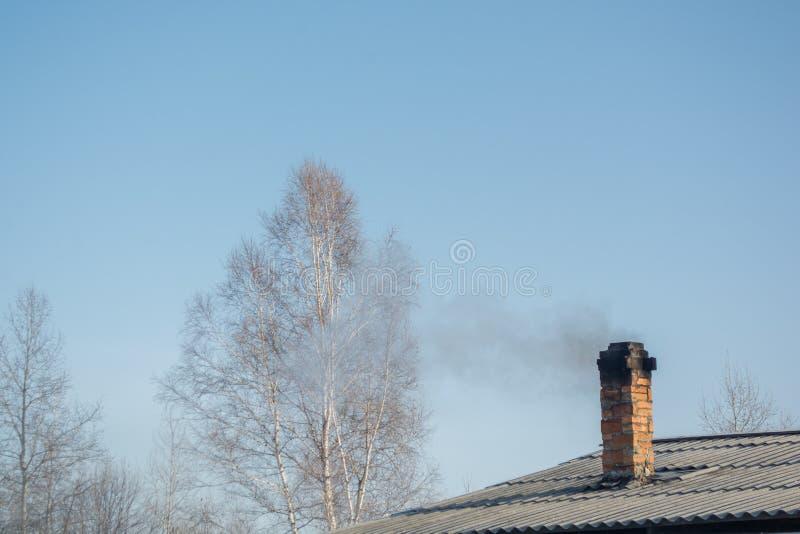 Röka röret på ett snöig tak i en kall vinterdag fotografering för bildbyråer