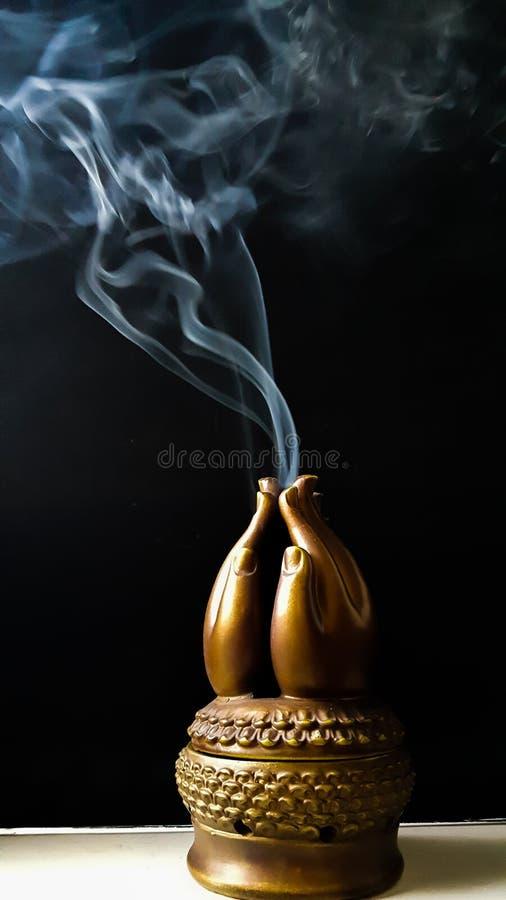 Rökelserök från bränning i träbönhänder arkivfoton