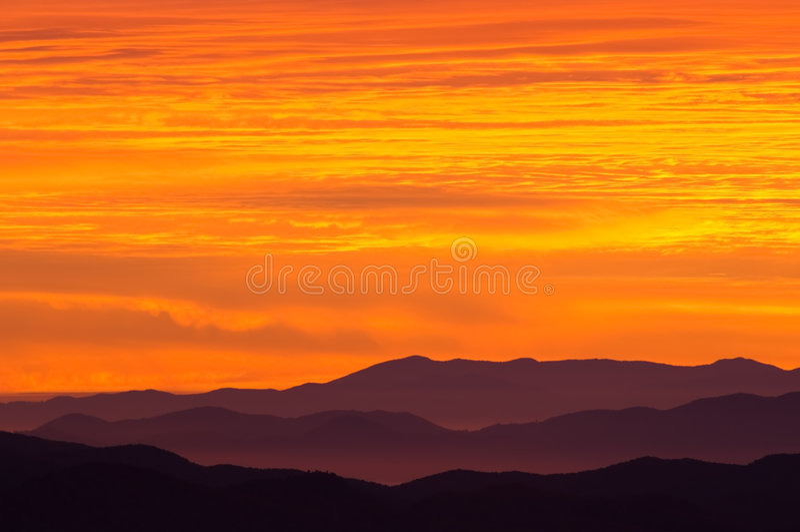 rökig soluppgång för stora berg arkivbild