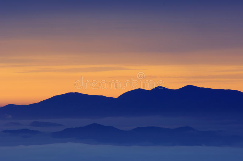 rökiga stora berg för gryning arkivbild