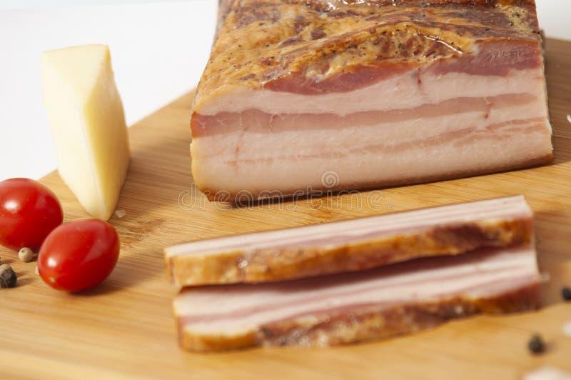 Rökt bacontjock skiva på skärbrädan som skivas med grönsaker arkivbilder