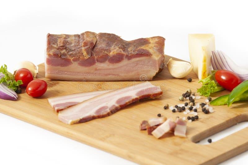 Rökt bacontjock skiva på skärbrädan som skivas med grönsaker royaltyfri bild