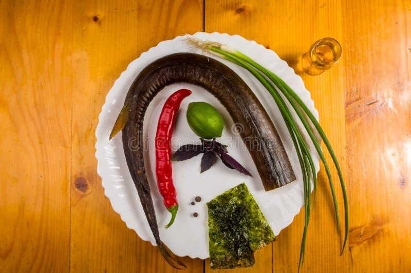 rökt garfish med limefrukt, basilika, salladslökar, chili, norichiper, kryddor, olivolja i en vit keramisk maträtt, på en trätabe fotografering för bildbyråer
