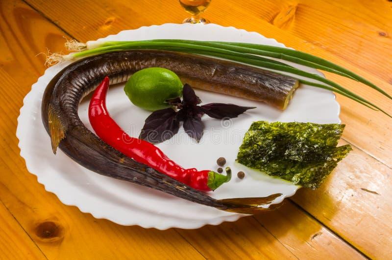 rökt garfish med limefrukt, basilika, salladslökar, chili, norichiper, kryddor, olivolja i en vit keramisk maträtt, på en trätabe arkivbild