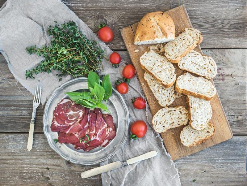 Rökt kött i tappningsilverplattan med nya basilika, körsbär-tomater och brödskivor över lantligt trä royaltyfria foton