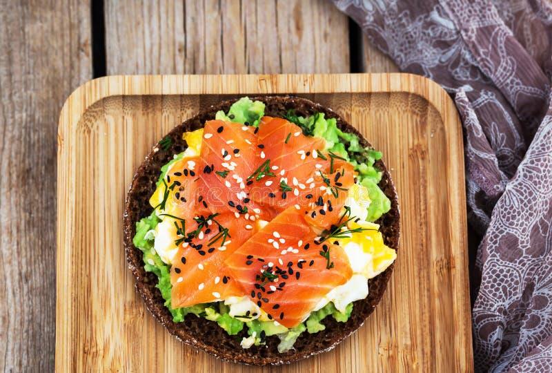 Rökt lax, förvanskade ägg och knaprigt rostat bröd för avokadoråg arkivbild