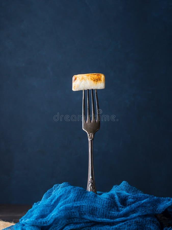 Rökt marshmallow på gaffel på mörk bakgrund arkivfoton