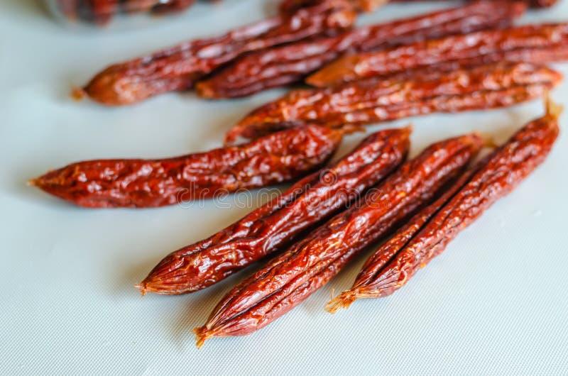 Rökt salami på en ljus bakgrund Selektiv mjuk fokus N?rbild royaltyfria foton