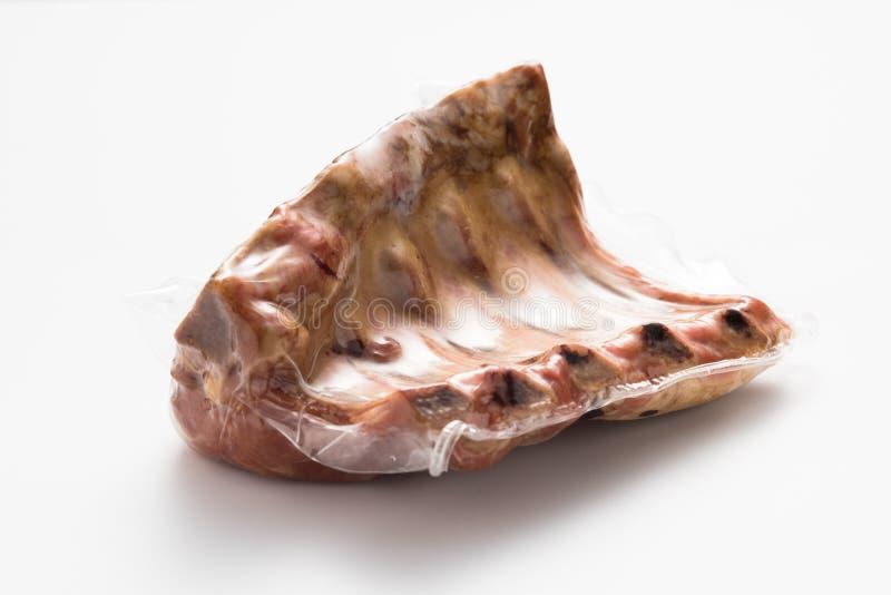 Rökte grisköttstöd som är vakuumpackade på en vit bakgrund royaltyfria foton