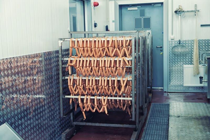Rökte korvar på livsmedelsförädlingväxten som tonas arkivfoto