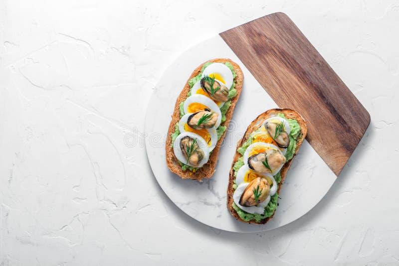 Rökte musslor och avokadorostade bröd, vit bakgrund, kopieringsutrymme royaltyfria bilder
