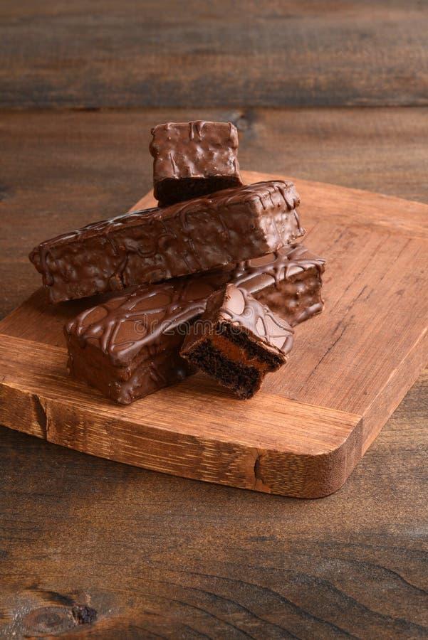 Rör av chokladkräm, fyllda kakor av gris på styckskivor arkivfoto