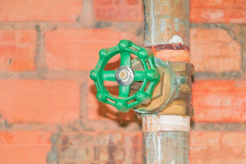 Rör för klapp för stål för skarv för vattenventilrörmokeri gammalt med den gröna knoppen på tegelstenbakgrund arkivbilder