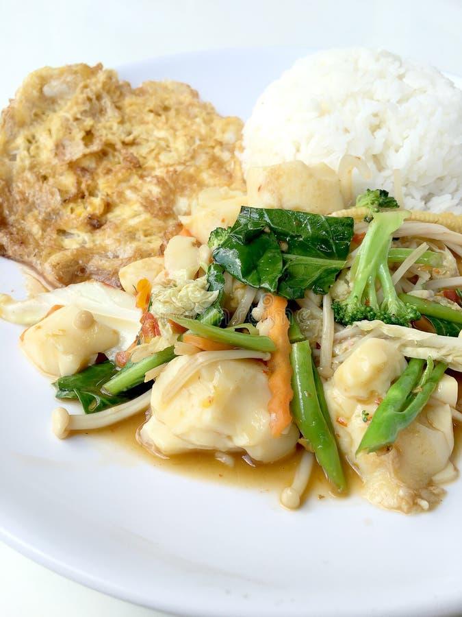 Rör grönsaker med tofuen i kinesisk stil med skysås och thai stilomelett med ris i den vita plattan på bakgrund Vegetari royaltyfria foton