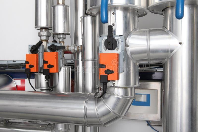 Rör och vattenkranventiler av uppvärmningsystemet i ett kokkärlrum royaltyfri fotografi