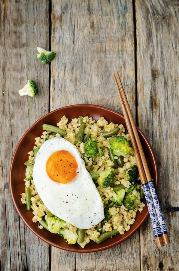 Rör stekt hirs med broccoli, haricot vert och det stekte ägget arkivfoto