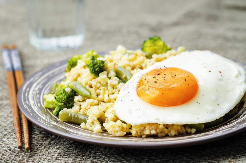 Rör stekt hirs med broccoli, haricot vert och det stekte ägget arkivfoton