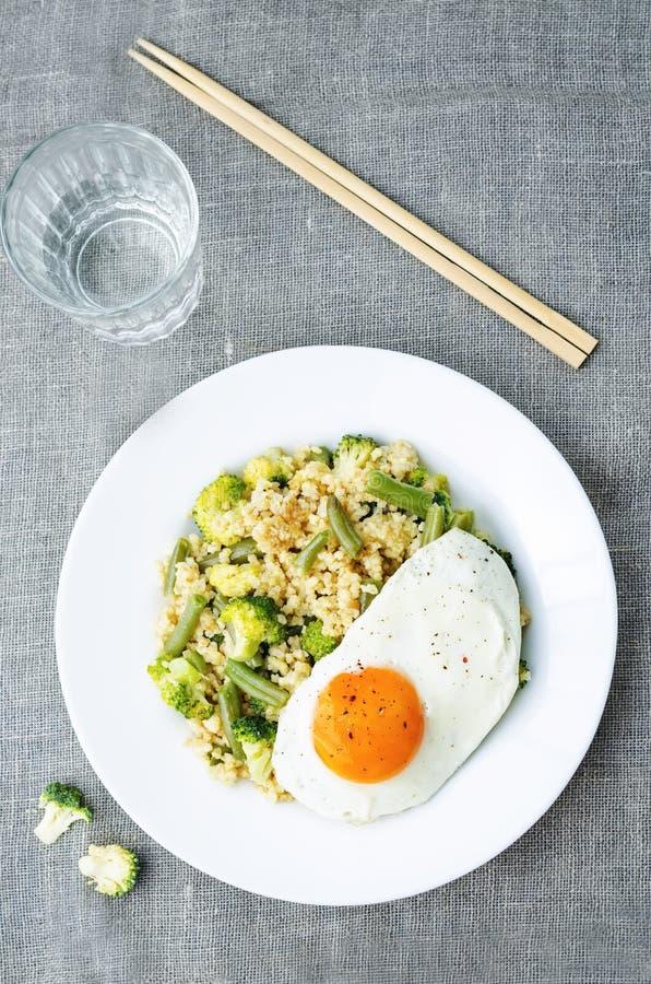 Rör stekt hirs med broccoli, haricot vert och det stekte ägget royaltyfria bilder