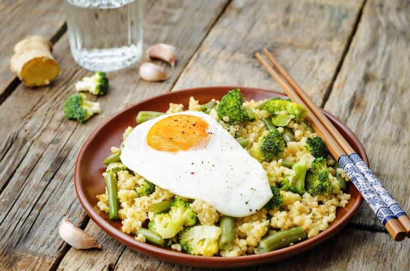 Rör stekt hirs med broccoli, haricot vert och det stekte ägget royaltyfri foto