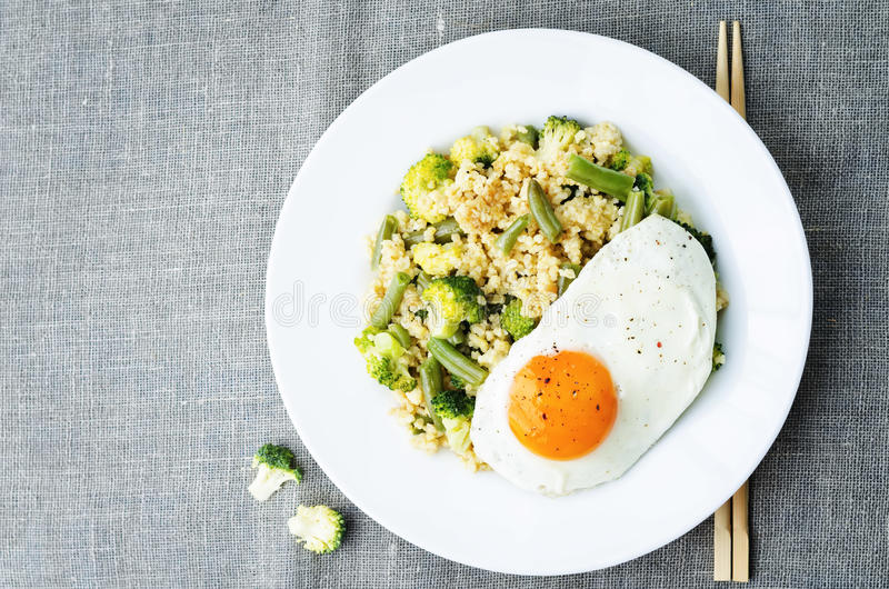 Rör stekt hirs med broccoli, haricot vert och det stekte ägget royaltyfri fotografi