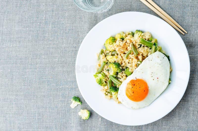 Rör stekt hirs med broccoli, haricot vert och det stekte ägget royaltyfri bild