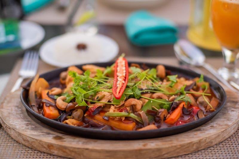 Rör stekt kyckling med kasjuer i en panna asiatisk mat royaltyfri foto