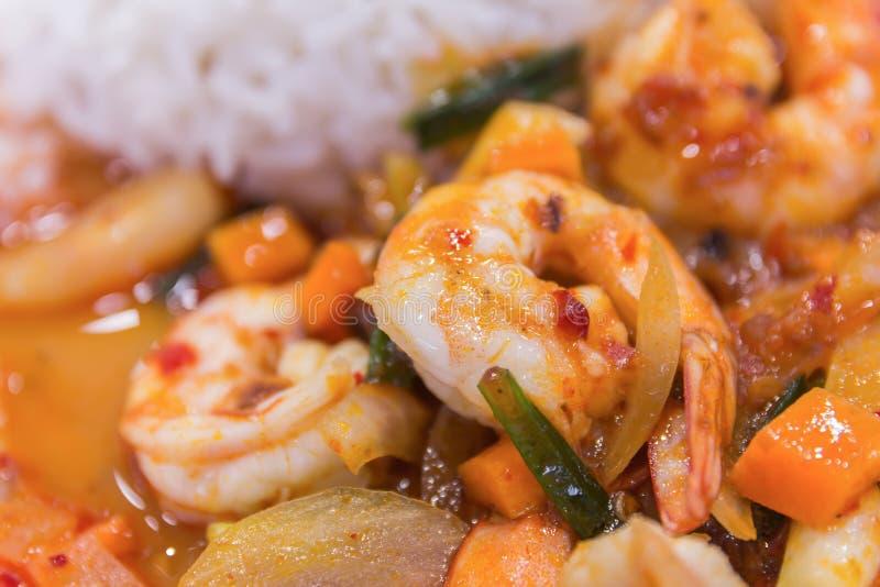 Rör stekt räka i thai röd stekt currydeg med ris och arkivbilder
