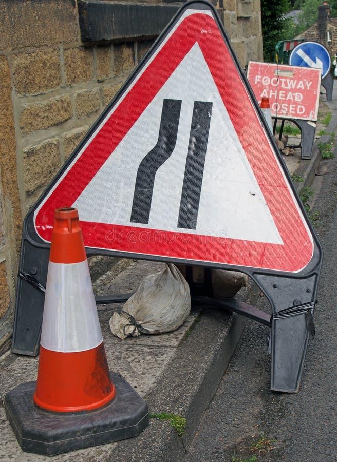 Röra av tillfälligt varnings- och riktningstecken på sidan av en smal landsväg, medan reparationsarbete bärs ut royaltyfri fotografi