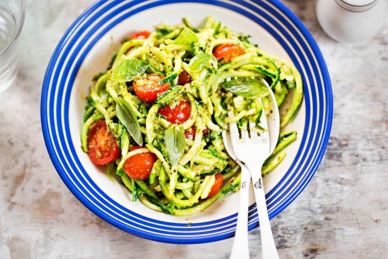 Röra sig i spiral zucchini med grön pesto och körsbärsröda tomater royaltyfria foton