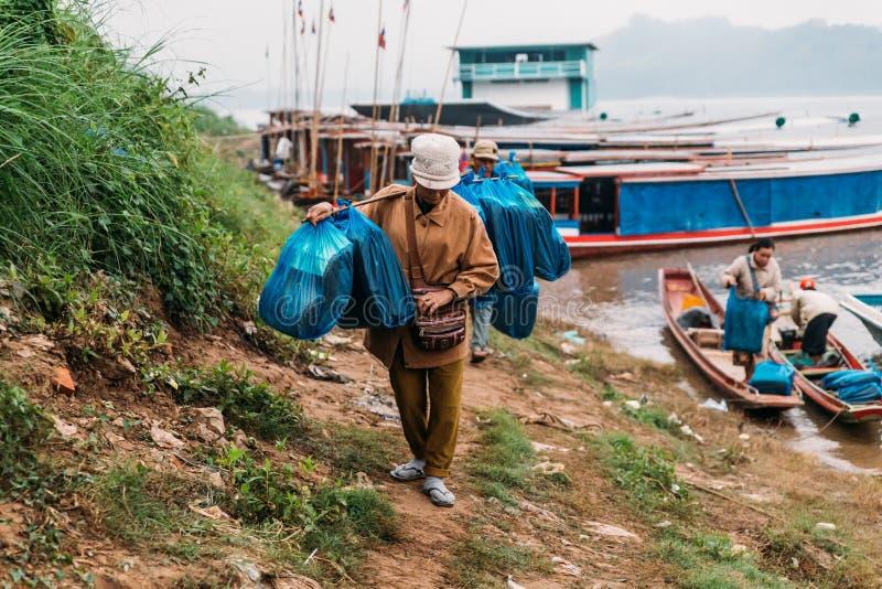 Rörande artiklar för folk till landet med fartyget i floden på Luang Prabang, Laos arkivfoto