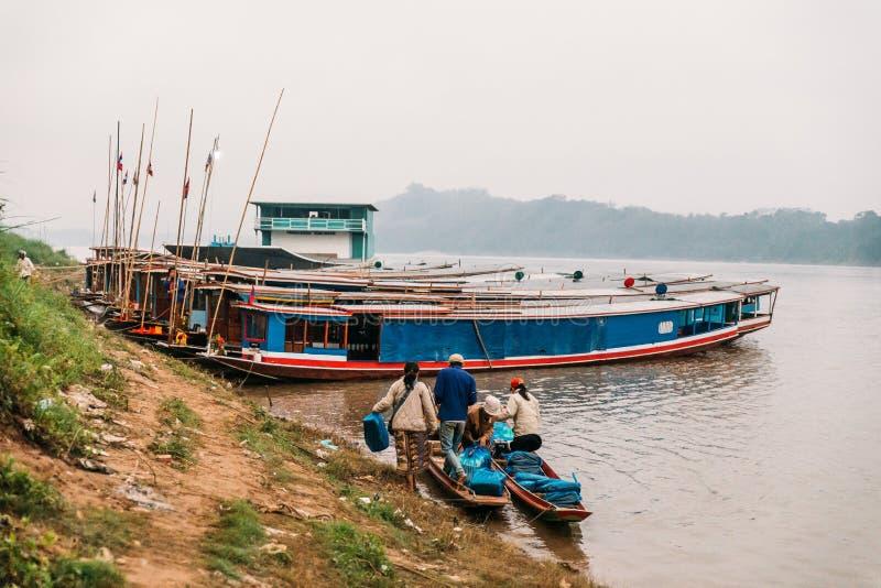 Rörande artiklar för folk till landet med fartyget i floden på Luang Prabang, Laos royaltyfri fotografi