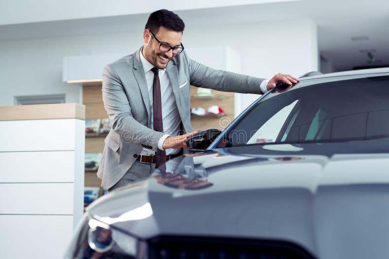 Rörande bil för lycklig man i auto show eller salong arkivbild