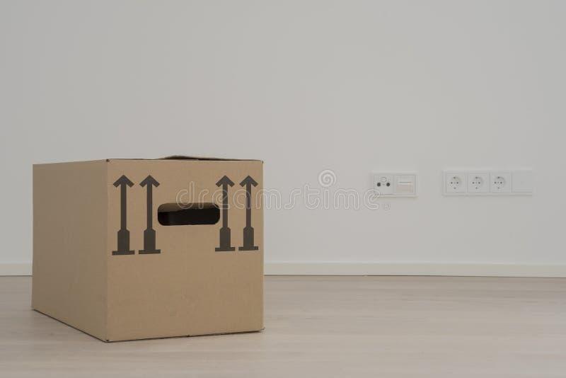 Rörande förpackande ask i tomt vitt rum, elektriska uttag i bakgrund arkivbilder