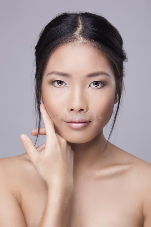 Rörande hud för asiatisk skönhetskincarekvinna på framsida arkivbild