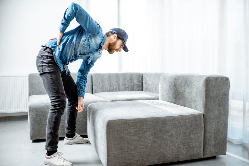 Rörande soffa för man med tillbaka knip arkivbild