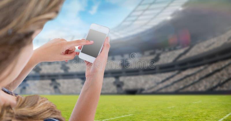 Rörande tom skärm för kvinna av mobiltelefonen på stadion royaltyfri fotografi